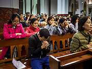 24 DECEMBER 2017 - HANOI, VIETNAM:  People pray during Christmas Eve services in St. Joseph's Cathedral in Hanoi. The commercial and gift giving aspect of Christmas is widely celebrated in Vietnam and Vietnam's 5+ million Catholics celebrate the religious aspects of Christmas.   PHOTO BY JACK KURTZ
