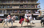 Local chiefs ride horses through the streets of Sabon Gari the Christian area of Kano during the Durbar Fantasia..The Durbar Fantasia, is the moment where The Husa residents of Kano wear traditional dress, their local leaders and chiefs mount horses, and together with their militias display allegiance and homage to their leader, the Emir of Kano. This takes place after Ramadan. The Emir is Kano's State official political and economic feudal leader, everyone seeks to be in his pleasure, otherwise they reap the consequences..Kano is the largest Muslim Husa city, under the feudal, political and economic rule of the Emir. Kano and the other eleven northern states are under Islamic Sharia Law which is enforced by official state apparatus including military and police, Islamic schools and education, plus various volunteer Militia groups supported financially and politically by the Emir and other business and political bodies. 70% of the population live below the poverty line. Kano, Kano State, Northern Nigeria, Africa