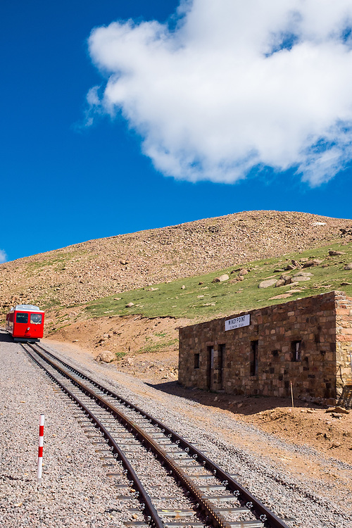A Cog Railroad car passes the rail switch and station house at Windy Point on Pikes Peak in Colorado.
