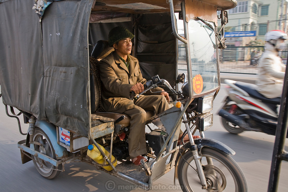 A disabled Vietnamese War veteran friend of Vietnamese veteran Thuan Nguyen Van drives his motorized cart in Hanoi, Vietnam. ( Thuan Nguyen Van is featured in the book What I Eat: Around the World in 80 Diets.)  Today, as war veterans, they have special dispensation to operate motorized carts on the streets of Hanoi. They use them to haul goods from one place to another around the city.