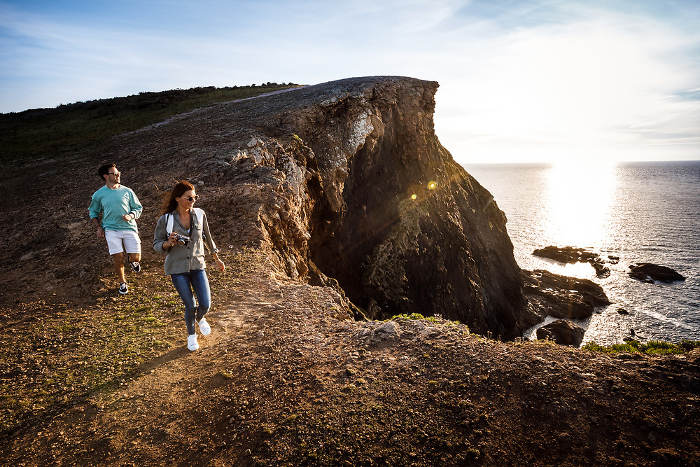 Couple walking and exploring the cliff paths and headland near Plemont in Jersey, Channel Islands, at sunset