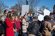 Washington, DC, USA -- March 4, 2020. Counter protesters at an abortion rights rally wear red tape over their mouths;  a photo journalist takes close-up photos.