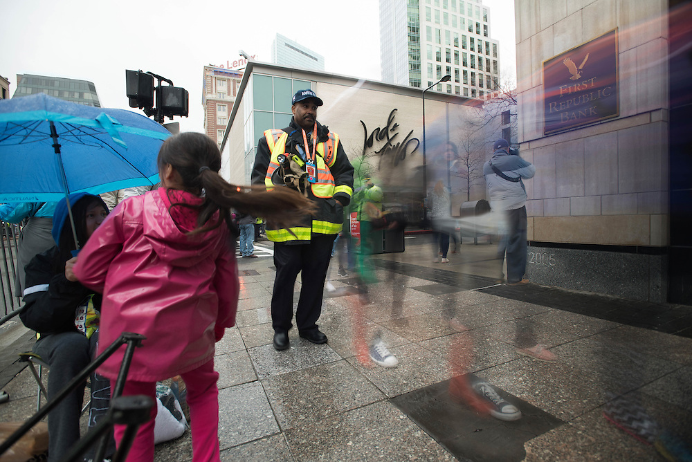 Taken Monday, April 20th, 2015 from 9:15-9:28AM.  Found and © by Mike Ritter.<br /> <br /> This was Marathon Monday 2015.  The weather was rainy.  A kind fellow spectator passed me a plastic bag to place over my camera.  While I shot, the announcements of the beginning heats of runners were announced.  A fireman walks through the crowd with police officers in the background.  A photographer takes photos up Ring Road where a security checkpoint was.  A camera hangs off the roof of Lord and Taylor.  The second bomb went off almost directly across Boylston St.  Maybe that camera helped track down the Tsarnaev brothers.