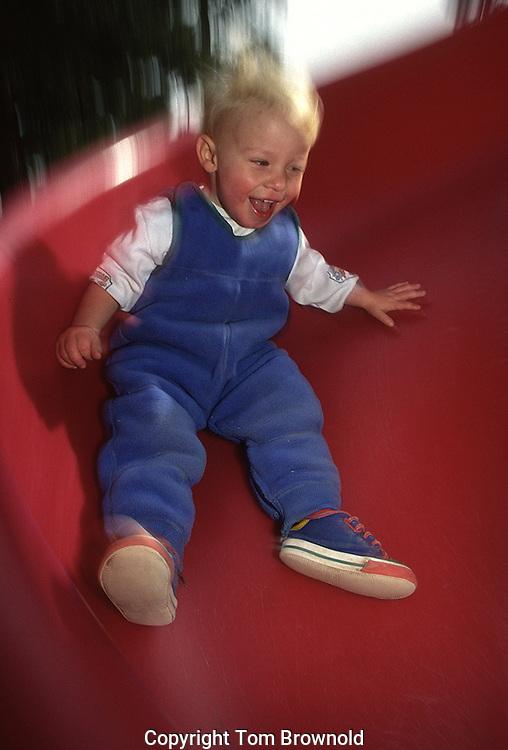 child on a sliding board