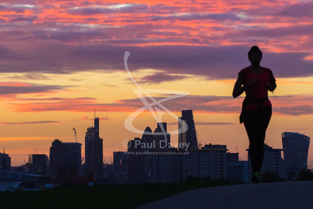 Primrose Hill, London, September 27th 2016. A runner  on Primrose Hill's silhouette looms over the backdrop of the City's skyscrapers as dawn breaks over London. ©Paul Davey<br /> FOR LICENCING CONTACT: Paul Davey +44 (0) 7966 016 296 paul@pauldaveycreative.co.uk
