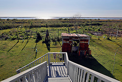 04 March 2016. Isle de Jean Charles, Louisiana.<br /> Vanishing land. First climate refugees in the USA. Isle de Jean Charles Band of Biloxi-Chitimacha Indians.<br /> Looking from the back porch of Wenceslaus Billiot's house. 'It used to be all you could see was trees and woods,' said Wenceslaus, father of deputy chief Boyo Billiot. The proud WW2 veteran and tribal elder may be forced to leave the home he has known all his life. The tribe has recently been awarded $52 million to resettle on higher ground as more and more of their land is consumed by erosion from the Gulf of Mexico.<br /> Photo©; Charlie Varley/varleypix.com