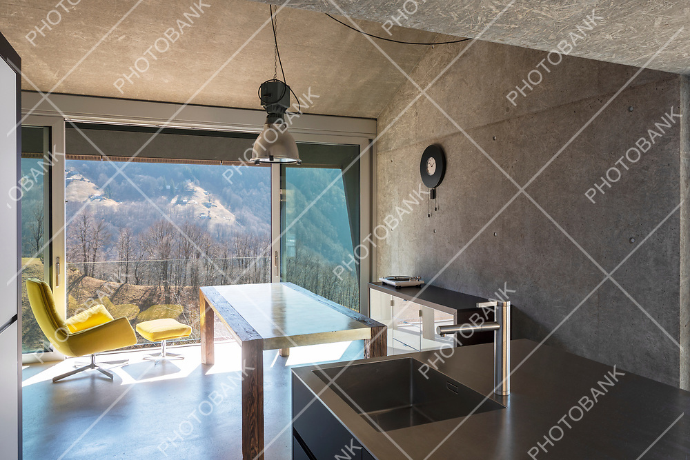 Detail of modern kitchen island, sink. Interior of a beautiful modern house, with a table, a yellow armchair and a view of nature. Nobody inside