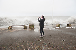**SERIES OF 4 IMAGES** © London News Pictures. 01/02/2014. Aberystwyth, UK. A woman attempts to escape being hit by a wave while taking a photograph at Aberystwyth seafront in Wales, UK. Locals are braced for further storms battering the coastline at Aberystwyth seafront which was badly damaged by strong storm weather just a few weeks ago. Photo credit: Keith Morris/LNP