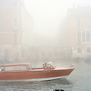 A motor boat driving down the Grand Canal on a misty morning in Venice, Italy