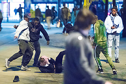 © Licensed to London News Pictures . 07/04/2017 . Manchester , UK . 6th in a sequence . Five youths on one as a fight breaks out in which a man's head is kicked and stamped upon , in Piccadilly Gardens . Greater Manchester Police have authorised dispersal powers and say they will ban people from the city centre for 48 hours , this evening (7th April 2017) , in order to tackle alcohol and spice abuse . Photo credit : Joel Goodman/LNP