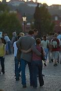 Czeck Republic - Prague, Couple walks across Charles bridge, evening glow after sunset.