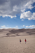 Two boys walk into the Great Sand Dunes with their snowboards. The wilderness area that covers the dunefield is popular for skiers and snowboarders. Great Sand Dunes National Park and Preserve, Colorado.