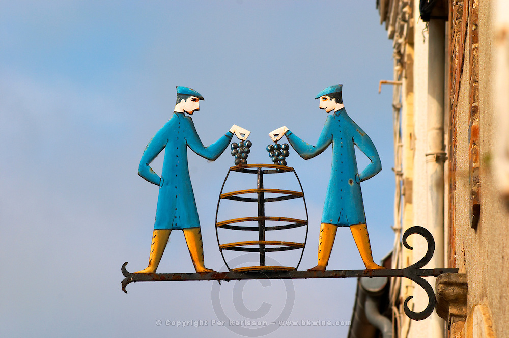 A wrought iron painted sign that illustrates the theme of champagne and wine production: two men putting grape bunches in a transparent stylised vat barrel, the village of Hautvillers in Vallee de la Marne, Champagne, Marne, Ardennes, France