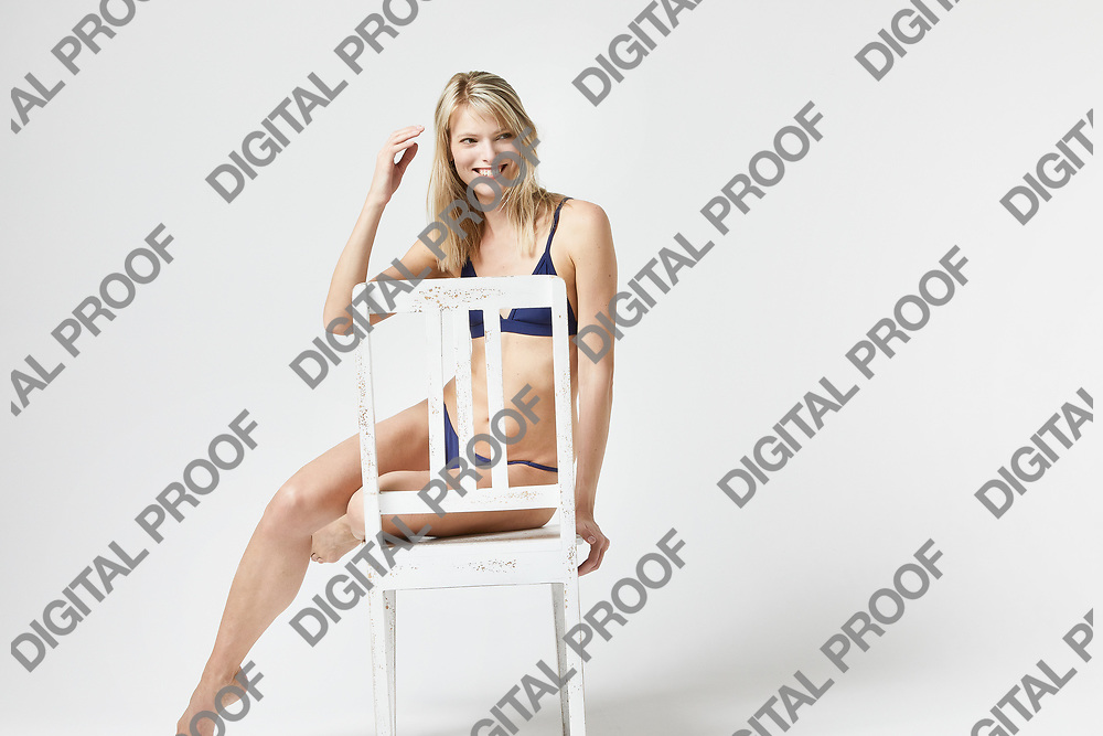 Portrait of a smiling woman looking confident seated in studio with a white background