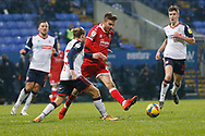 Bolton Wanderers Lloyd Isgrove clears from Crawley Town's Archie Davies during the EFL Sky Bet League 2 match between Bolton Wanderers and Crawley Town at the University of  Bolton Stadium, Bolton, England on 2 January 2021.
