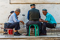 A group of elderly Uyghur men playing cards under a grape arbor in Turpan, Xinjing Province, China. Turpan is a small oasis town and former Silk Road outpost located in a depression 30m above sea level.