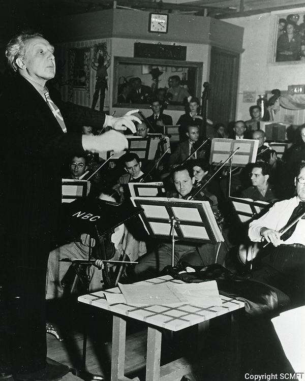 1943 Conductor, Leopold Stokowski conducts an orchestra at the Hollywood Canteen.