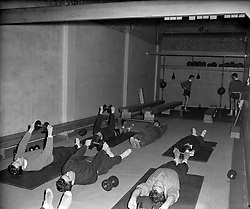 Tottenham players in the gym, exercising with weights.