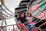 09 SEPTEMBER 2004 - WINDOW ROCK, AZ: Children on a midway ride during the 58th annual Navajo Nation Fair in Window Rock, AZ. The Navajo Nation Fair is the largest annual event in Window Rock, the capitol of the Navajo Nation, the largest Indian reservation in the US. The Navajo Nation Fair is one of the largest Native American events in the United States and features traditional Navajo events, like fry bread making contests, pow-wows and an all Indian rodeo.  PHOTO BY JACK KURTZ