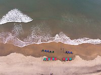 Top down aerial view of waves on mandrem beach in Goa state of India.