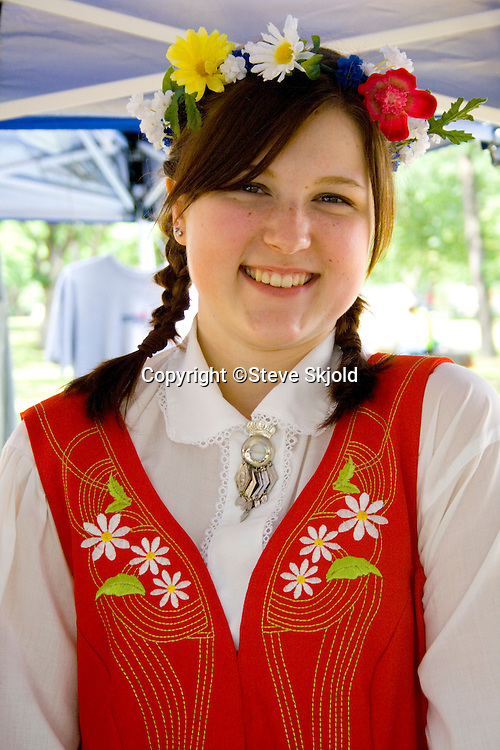 Happy teen wearing garland and costume of Sweden. Svenskarnas Dag Swedish Heritage Day Minnehaha Park Minneapolis Minnesota USA