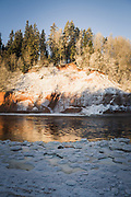 Sunlit sandstone cliff-face of Ķūķu iezis in cold and frost covered winter morning with various ice formations next to river Gauja in front of it, Gauja National park (Gaujas nacionālais parks), Latvia Ⓒ Davis Ulands | davisulands.com