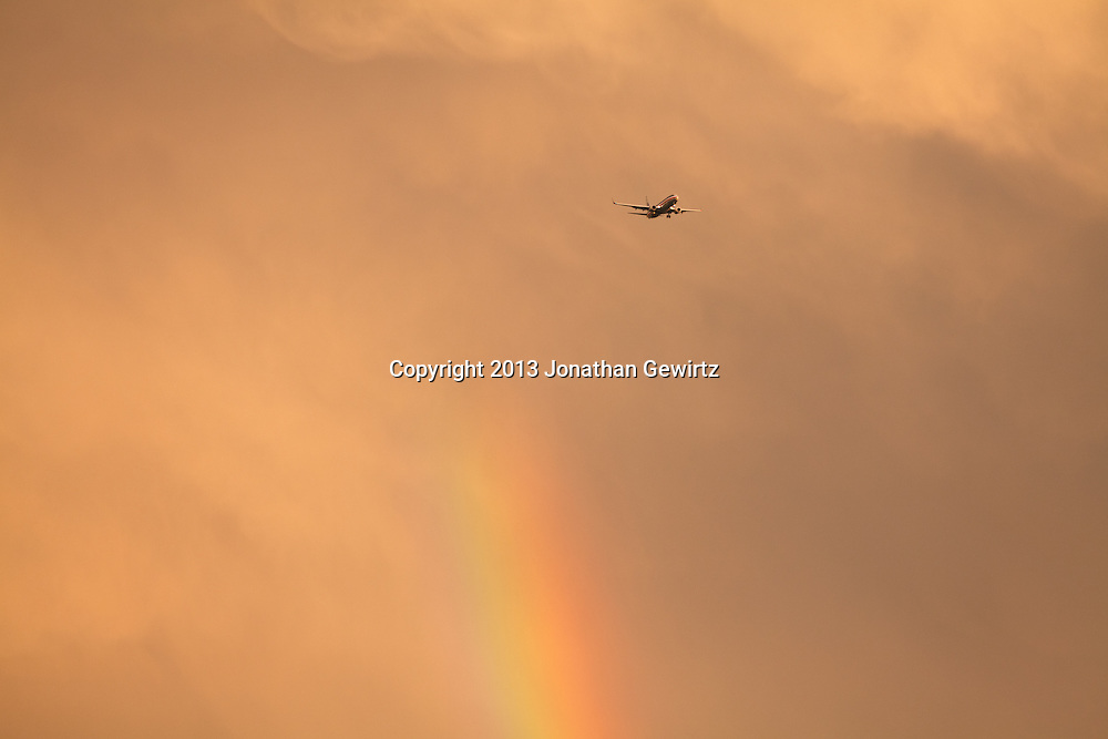 A jet airliner flies past a rainbow in stormy skies. WATERMARKS WILL NOT APPEAR ON PRINTS OR LICENSED IMAGES.