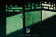 Shadows falling on green doors.