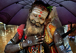 TRIMBAKESHWAR,INDIA, AUGUST 8:  A Hindu pilgrim poses at a shrine at Trimbakeshwar during the month long Kumbh Mela in in India, August 8, 2003. Kumbh Mela, a famous Hindu festival, is expected to bring  more than three million pilgrims and foreign tourists. (Photo by Ami Vitale/Getty Images)