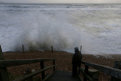 © Licensed to London News Pictures. 06/01/2014, Milford on Sea, UK. A man watches a wave batter the coast at Milford on Sea, England , Monday, Jan. 6, 2014. Part of UK continue to be affected by floods and strong wind. Photo credit : Sang Tan/LNP