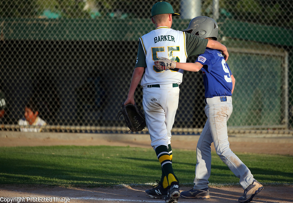 In a supreme show of sportsmanship, Capitola-Soquel A's pitcher Bryce Barker gives a hug to Santa Cruz Cubs batter Cameron Clark as Clark makes his way to first after being hit by a fastball thrown by Barker during the District 39 Little League minors championship game played at Franich Park in Watsonville, California on Tuesday June 19, 2018. Santa Cruz won the game 8-0 to claim the title.<br /> Photo by Shmuel Thaler <br /> shmuel_thaler@yahoo.com www.shmuelthaler.com