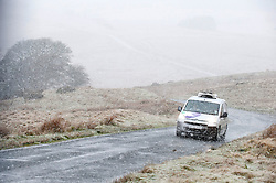 © Licensed to London News Pictures. 21/03/2017. Mynydd Epynt, Powys, Wales, UK. On the Spring Equinox, motorists drive along a minor road in snow and strong winds which arrived this afternoon on the high moorland of the Mynydd Epynt range between Garth and Brecon in Powys, Wales, UK. Photo credit: Graham M. Lawrence/LNP