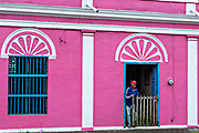A man comes out from a brightly painted colonnaded style home in Tlacotalpan, Veracruz, Mexico. The tiny town is painted a riot of colors and features well preserved colonial Caribbean architectural style dating from the mid-16th-century.