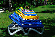 Eleven plastic lounge chairs, a young woman asleep on the furthest. Kuta, Bali, Indonesia.