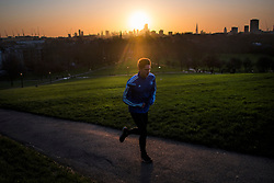 © Licensed to London News Pictures. 11/02/2020. London, UK. A jogger at sunrise in Primrose hill in North London. Large parts of the UK are recovering from the affects of storm Ciara which caused heavy flooding and damage from high winds. Photo credit: Ben Cawthra/LNP