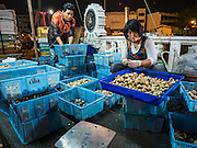 "21 DECEMBER 2015 - BANGKOK, THAILAND: A vendor sells fresh mushrooms from a stall near Pak Khlong Talat, also called the Flower Market. The market has been a Bangkok landmark for more than 50 years and is the largest wholesale flower market in Bangkok. A recent renovation resulted in many stalls being closed to make room for chain restaurants to attract tourists. Now Bangkok city officials are threatening to evict sidewalk vendors who line the outside of the market. Evicting the sidewalk vendors is a part of a citywide effort to ""clean up"" Bangkok.       PHOTO BY JACK KURTZ"