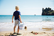Child standing in the sand at Beauport Beach, holding a bucket, watching the sea washing over his sand castles on a sunny summer day in Jersey, Channel Islands