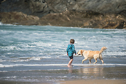 A young boy and his pet dog playing at Fistral Beach in Newquay, Cornwall.