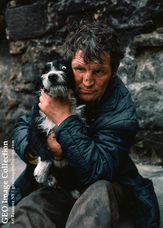 An indigent and forelorn Scotsman holds his scruffy dog on street in Glasgow. The man is alcoholic and his face bears marks of fighting.