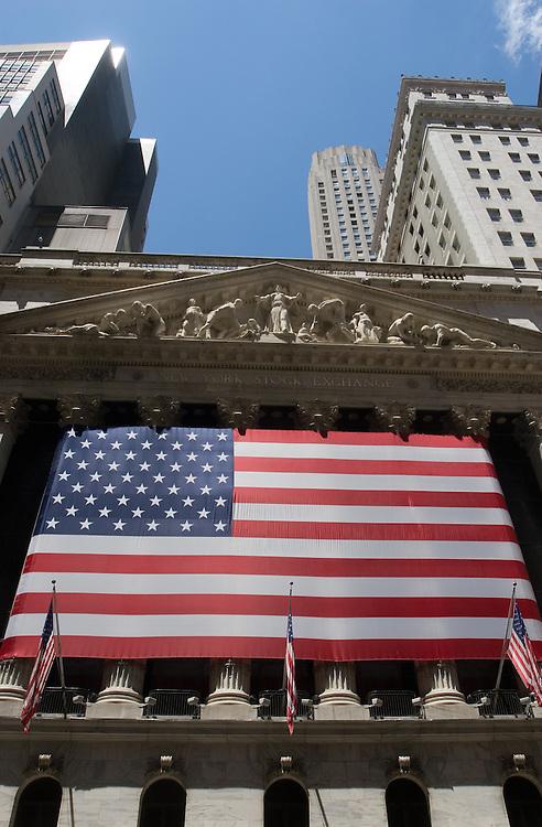 Fachada del famoso edificio de la Bolsa, en Wall Street, decorado por una enorme bandera americana.
