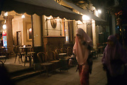 A traditionally dressed woman walks past a traditional coffee house or Ahwah near the Khan al-Khalili in Cairo, Egypt
