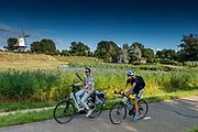 Een racefietser haalt een andere fietser in bij de korenmolen De Koe bij de Langendijk in Veere. De stellingmolen is gebouwd in 1909.<br /> <br /> A road cyclist passes a woman on a Dutch bike near De Koe flour mill at the Langendijk in Veere. The scaffolding mill was built in 1909.