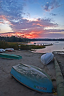 Dinghies rest on the beach as the sun sets at Meetinghouse Pond in East Orleans