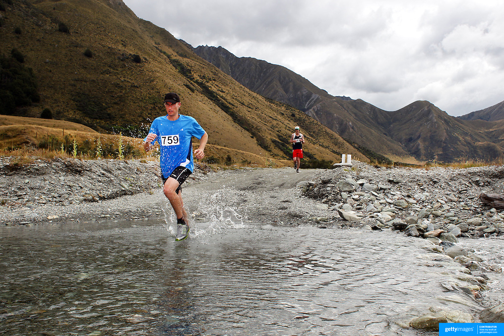 Runner Jeff Kennedy crosses Moke Creek on the Ben Lomond High Country Station during the Pure South Shotover Moonlight Mountain Marathon and trail runs. Moke Lake, Queenstown, New Zealand. 4th February 2012. Photo Tim Clayton