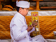 """08 AUGUST 2017 - UBUD, BALI, INDONESIA: A Hindu priest leads a service during a ceremony to honor a family temple in Ubud, Bali. Balinese Hindus have a 210 day calender and every almost every family compound on Bali has a family temple. Once a year (or every 210 days) families celebrate the """"birthday"""" of their temple with a ceremony.     PHOTO BY JACK KURTZ"""