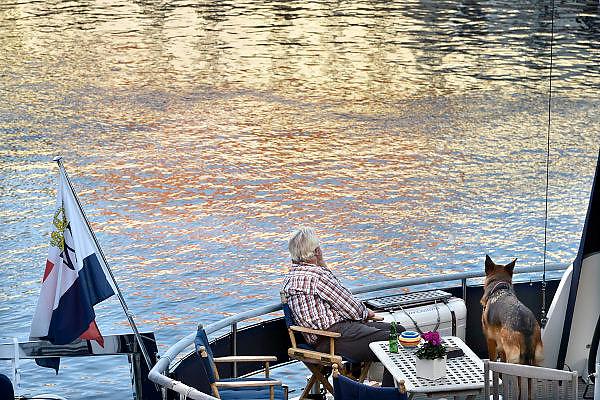 Nederland, Heusden, 18-10-2014Een oudere man, geniet samen met zijn hond op zijn boot van zijn oude dag. Vandaag werd een record, weerrecord, gebroken. Het was de warmste 18 oktober sinds de weermetingen begonnen.Foto: Flip Franssen/Hollandse Hoogte