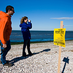 A young couple watches for piping ploves on Long Beach in Stratford, Connecticut.  Adjacent to the Great Meadows Unit of McKinney National Wildlife Refuge.