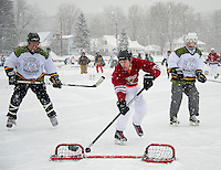 Dave Beaulieu sinks a goal against the Moose Island Marauders during tournament action on Meredith Bay Friday at the New England Pond Hockey Classic.  (Karen Bobotas/for the Laconia Daily Sun)