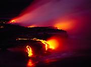 Steam rising off molten lava flowing into the sea, Pali Uli, Hawaii Volcanoes National Park, Big Island of Hawaii.
