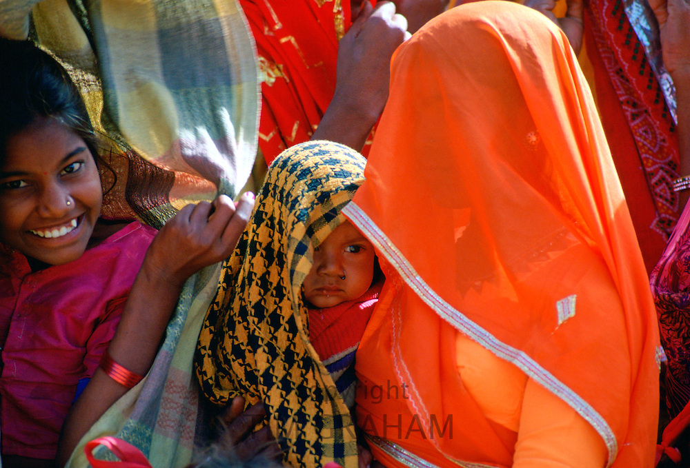 A  veiled woman, in brightly coloured robes holding her baby while watching a village festival in Nalu, Rajasthan, India